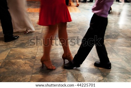 This photo shows a woman in high heels and skirt teaching a young boy how to dance, it's filled with motion as they are ballroom dancing. - stock photo