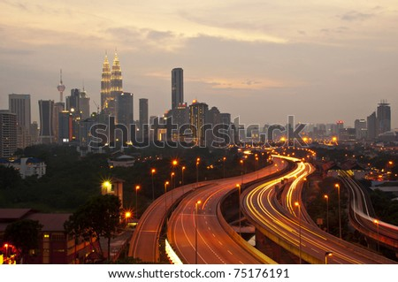 This scenario Kuala Lumpur twin towers, taken with slow shutter speed to get the light trail from the highway traffic in the evening. lightrail view of Kuala Lumpur city. - stock photo