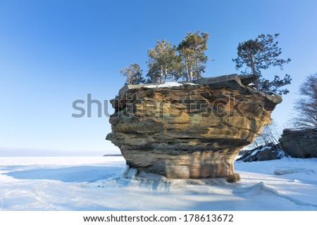 This sea stack of rock, known as Turnip Rock, rises from the ice of a frozen Lake Huron in winter. It is located near the tip of the thumb in Port Austin Michigan - stock photo