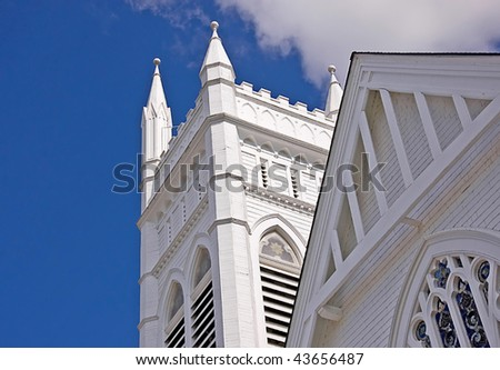 This shot is a portion of an ancient church steeple against a bright blue clear sky.