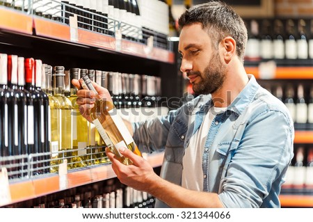 This should be fine. Side view of handsome young man holding bottle of wine and looking at it while standing in a wine store  - stock photo