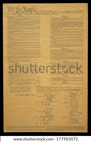 This shows the entire original U.S. Constitution on its faded parchment paper. The document begins with he phrase We The People and shows the signatures at the end of the historic document. - stock photo