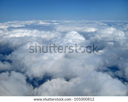 This stock image is of white, puffy clouds and blue sky above the clouds, from a mid air perspective, blue sky above and clouds below.