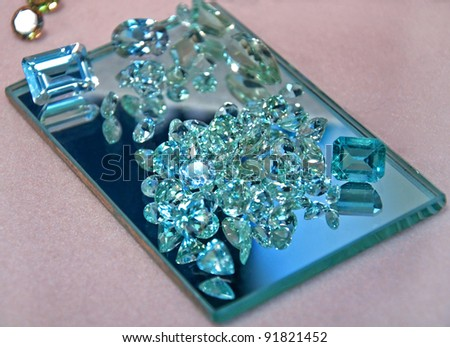 This stock image shows loose aquamarine gemstones in both cut rectangular shapes and round diamond cut shapes on a rectangle mirror, full of sparkle and shine.