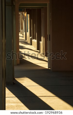 This strong sunlight of this Santa Fe New Mexico morning highlights the strong textures and shadows of the adobe buildings lining the street in the historical downtown plaza. - stock photo