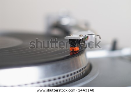 This stylish 20-years old turntable is playing disk. The tone-arm cartridge is in focus. You can put your logo and text on it. Very shallow DoF with focus on top of gray arm. - stock photo