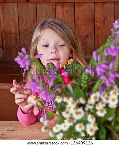 This sweet 4 year old girl is behind a cut flower bouquet, arranging the flowers.  Flowers are intentionally blurred to emphasize the child. - stock photo