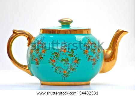 This turquoise and gold teapot has been in my family for many generations.  This isolated object on white background is a rare, unique item. - stock photo