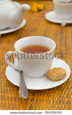 this vertical shot shows a Cup of tea and cookies spoon on a saucer set on a wicker table
