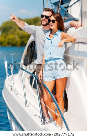 This view is amazing! Cheerful young couple looking away and smiling while standing on the board of yacht - stock photo