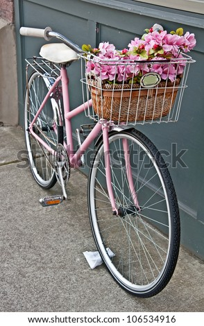 This vintage pink girls bicycle has beautiful pink flowers in a basket on the front of the bike.  Set in a vertical format on a sidewalk.