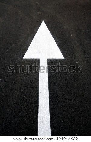 This way: strong up white arrow on black asphalt / tarmac Multiple metaphorical uses: goal hope solution decision judgment, leadership, business strategy, growth, personal development, yes, etc. - stock photo