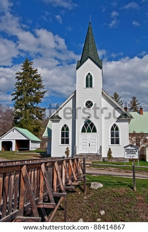This white classic turn of the century church was built in 1917 and is located in Havillah Washington in Okanogan County.  It's shot during the day and a cute small bridge in the foreground. - stock photo