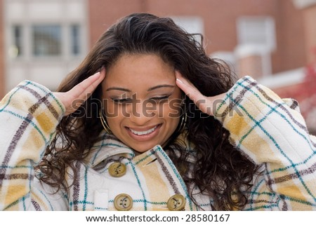 This woman is experiencing an intense amount of stress or possibly a headache. - stock photo