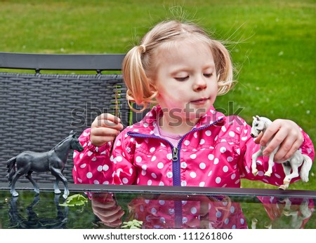 This 3 year old Caucasian preschool aged girl is playing with toy plastic horses outside.  She has blond pigtails, and wearing a pink and white polka dotted raincoat.  Classic childhood moment. - stock photo