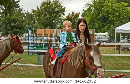 This 1 year old toddler girl is riding a first pony ride with her mom walking beside her.  Rural lifestyle family image. - stock photo