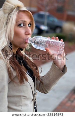 This young blonde female is drinking some bottled water.