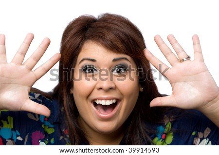 This young hispanic woman looks totally and completely surprised with her hands up in the air.