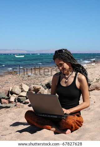 This young woman can be a professional freelancer or a student studying outdoors. She sits on a beach and uses her laptop. - stock photo