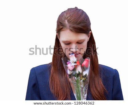 This young woman with long hair is smelling a package of rose.  She's in her early twenties, wearing a blue blazer, and isolated on white background.  Head and shoulders, front view Caucasian woman. - stock photo