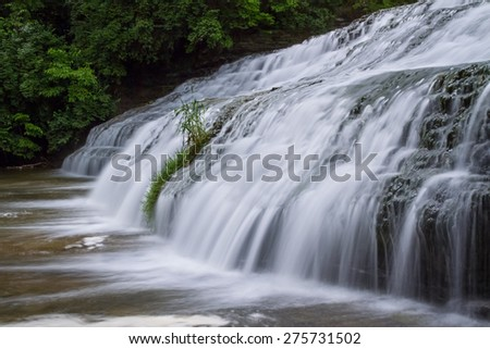 Thistlethwaite Falls, a wide waterfall photographed here with a long exposure, flows over rocky ledges in Richmond, Indiana. - stock photo