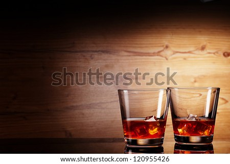 tho glasses of whiskey over wooden background - stock photo