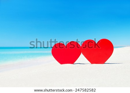 Tho red hearts on ocean beach sand - love concept for holidays - stock photo