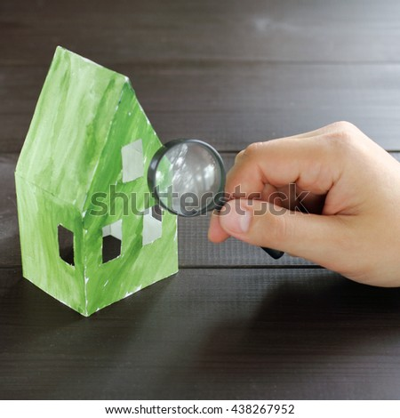 thorough inspection the concept of a magnifying glass green paper ecological home / check environmental performance - stock photo