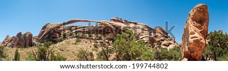 Thought to be the longest stone arch in the world, Landscape Arch is in the desert landscape of the Devil's Garden area of Arches National Park near Moab, Utah. - stock photo