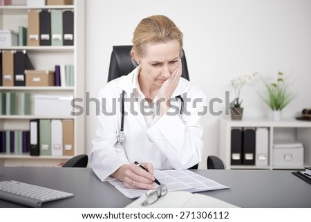 Thoughtful Adult Female Doctor Studying Medical Findings on a Paper While Sitting at her Table - stock photo