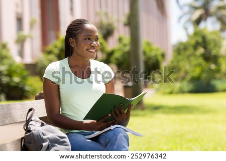 thoughtful african college girl sitting outdoors - stock photo