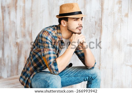 Thoughtful and romantic. Handsome young man wearing hat and looking away while sitting against the wooden wall  - stock photo