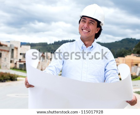 Thoughtful architect holding blueprints and wearing a helmet