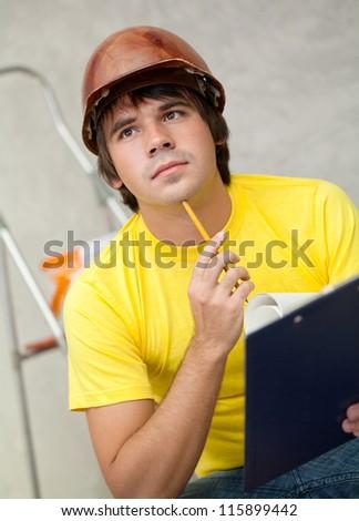 Thoughtful architector in helmet finding idea - stock photo