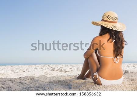 Thoughtful attractive brunette in white bikini sitting on the beach - stock photo