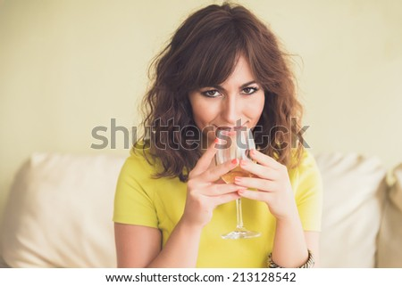 Thoughtful attractive young woman drinking a glass of champagne or white wine staring pensively down at the floor. - stock photo