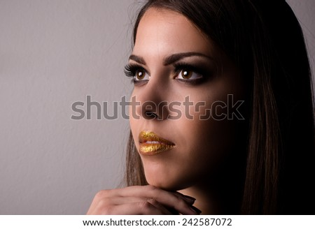 Thoughtful attractive young woman wearing makeup looking dreamily up into the air with her hand to her chin, closeup beauty portrait - stock photo