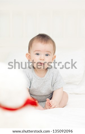 thoughtful baby boy sitting with  Teddy bear on the bed and looking attentively - stock photo