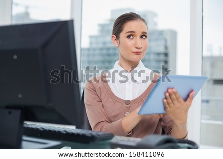 Thoughtful beautiful businesswoman in bright office using her tablet