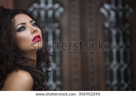 Thoughtful beautiful young brunette woman with curly hair and bright makeup looking away leaning and standing outdoor on brown brick wall background copyspace, horizontal picture - stock photo
