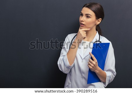 Thoughtful beautiful young doctor in white medical gown is holding a folder, looking away and thinking, standing against blackboard - stock photo