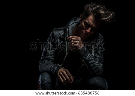 thoughtful biker sitting on chair against black studio background