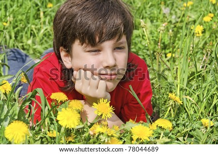 thoughtful boy boy lies on a lawn in flowers - stock photo