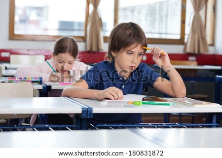 Thoughtful boy sitting at desk with classmate studying in background - stock photo