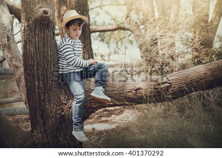 thoughtful boy sitting in a tree - stock photo