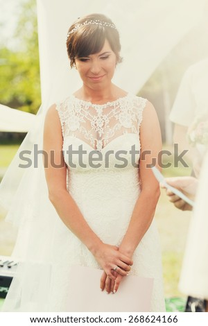 thoughtful bride in a white dress with lace at a wedding ceremony - stock photo
