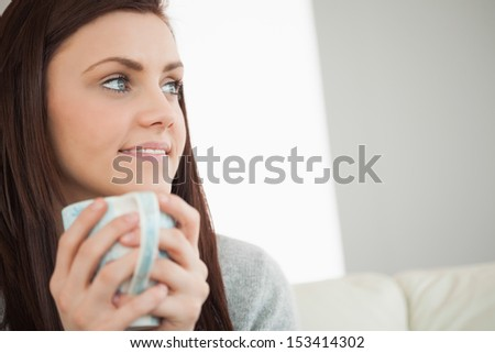 Thoughtful brunette holding a cup of coffee and looking away in a living room - stock photo