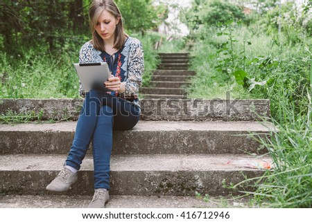 Thoughtful business girl looking to the digital tablet screen while sitting in nature.  Beautiful woman is watching movie on digital tablet, while relaxing after strolling. copy space - stock photo
