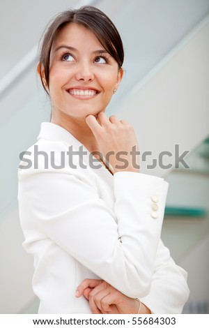 Thoughtful business woman at the office and smiling - stock photo