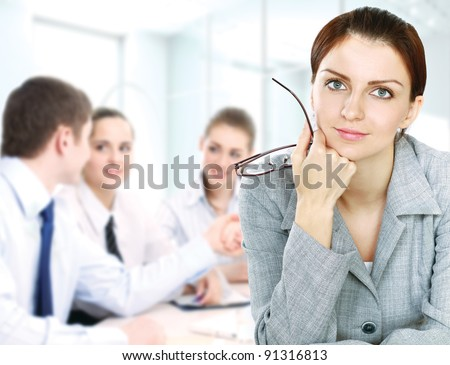 Thoughtful business woman smiling and looking away with colleagues - stock photo